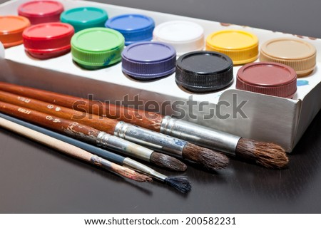 brushes and colored paint artist on gray background - stock photo