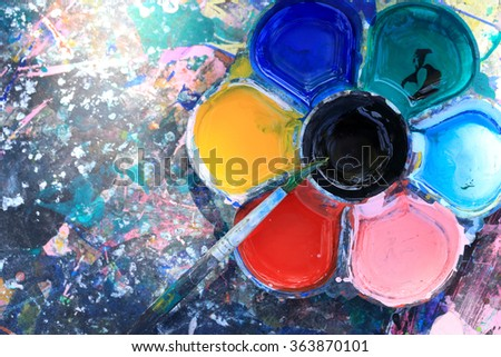 Brushes and dirty watercolor palette on dirty table. - stock photo