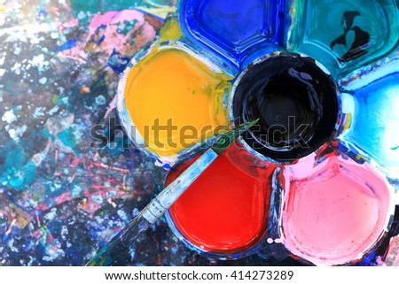 Brushes and dirty watercolor palette on grungy table. - stock photo