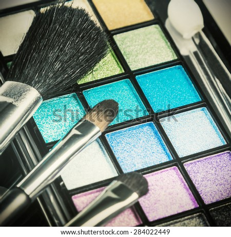 brushes and palette with eyeshadow for applying makeup . Focus in the middle of the frame on the green shadows. Shallow depth of field. Toned image - stock photo