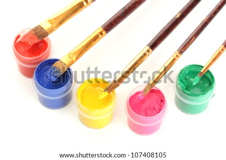 brushes on the jars with colorful gouache on white background close-up