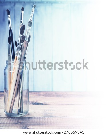 Brushes on wooden background with free space toned in blues. - stock photo