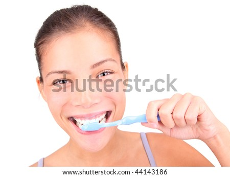 Brushing teeth. Closeup of woman actually brushing her teeth with toothpaste and a manual toothbrush. Beautiful mixed race asian / caucasian model. - stock photo