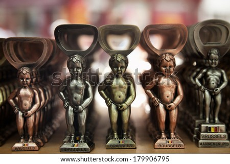 BRUSSELS - AUGUST 17: Small metallic replicas of Manneken Pis statue on sale as bottle openers on August 17, 2012 in Brussels, Belgium. This statue is a famous landmark and symbol of Brussels. - stock photo