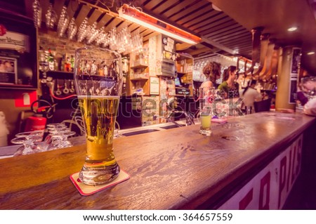 BRUSSELS, BELGIUM - 11 AUGUST, 2015: Beer glass sitting on bar counter inside Delirium Bar, selection of other beverages in background - stock photo