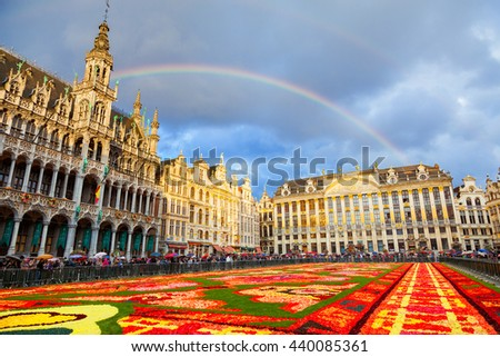 BRUSSELS, BELGIUM - AUGUST 15, 2014: Famous Grand Place during Flower Carpet Festival under cloudy sky with rainbow - stock photo
