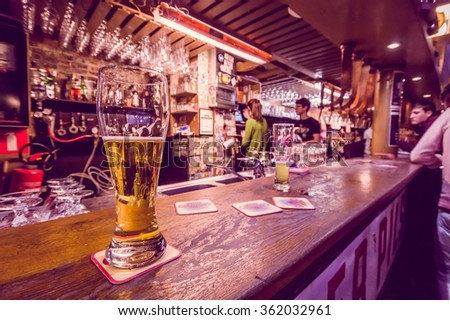 BRUSSELS, BELGIUM - 11 AUGUST, 2015: Glass of beer sitting on bar counter inside Delirium Bar, selection of other beverages in background. - stock photo