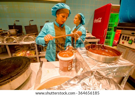 BRUSSELS, BELGIUM - 11 AUGUST, 2015: Happy lady working in belgian waffle store showing how to prepare and decorate this wonderful famous sweet experience  - stock photo