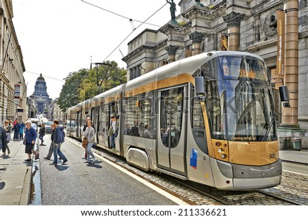 BRUSSELS, BELGIUM - AUGUST 15, 2014: The Royal Museum of Fine Arts with its stone columns and scenic sculptures makes the contrast with the modern tram on August 15 in Brussels. - stock photo