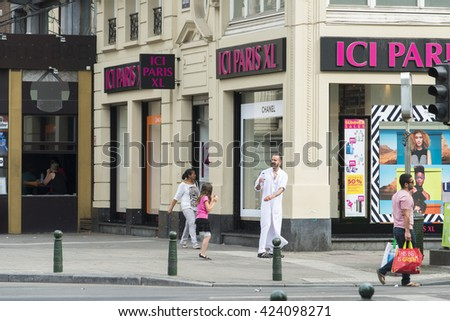 BRUSSELS, BELGIUM - JULY 4, 2015: A man in djellaba, jokes and plays with a girl in one of the streets of the city. - stock photo