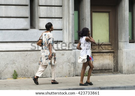 BRUSSELS, BELGIUM - JULY 4, 2015: A middle-aged woman and a girl walking on a street of the city. - stock photo