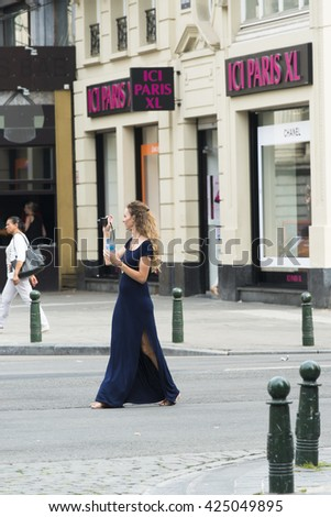 BRUSSELS, BELGIUM - JULY 4, 2015: A young woman in a long dress, takes pictures in the middle of the road, in one of the streets of the city. - stock photo