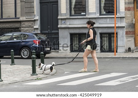 BRUSSELS, BELGIUM - JULY 4, 2015: A young woman with a dog walks on a pedestrian crossing in one of the streets of the city. - stock photo