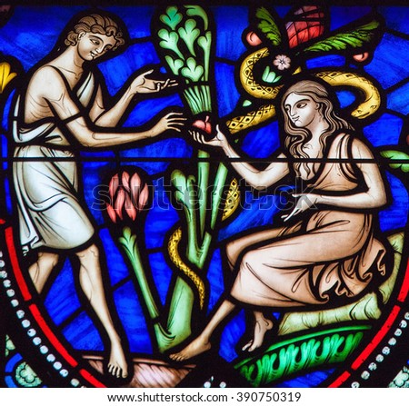 BRUSSELS, BELGIUM - JULY 26, 2012: Adam and Eve eating the Forbidden Fruit in the Garden of Eden on a stained glass window in the cathedral of Brussels.  - stock photo