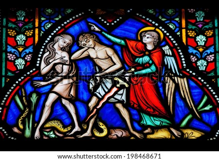 BRUSSELS, BELGIUM - JULY 26, 2012: Adam and Eve expelled from the Garden of Eden on a stained glass window in the cathedral of Brussels, Belgium.  - stock photo