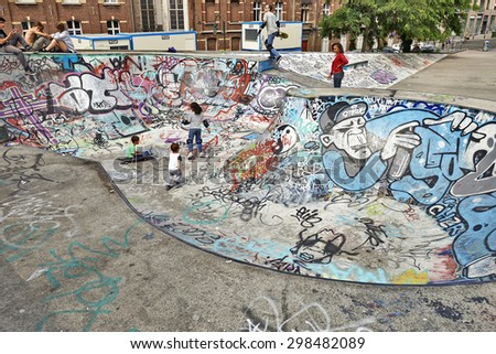 BRUSSELS, BELGIUM -18 JULY 2015: Some children playing in the bowl at the skate park in central Brussels.The Ursulines square is a public open square in skateboarding, BMX, inline skating, etc. - stock photo