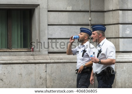 BRUSSELS, BELGIUM - JULY 4, 2015: Two police walk, while cool, with a canned drink, a hot summer day. - stock photo