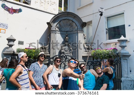 BRUSSELS, BELGIUM - JULY 10, 2015: Unknown american tourists making a selfie in front of Manneken Pis statue, one of the most famous Belgian and Brussels monuments and a symbol of the city - stock photo
