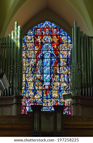 BRUSSELS, BELGIUM-JUNE 2, 2014: Stained glass window in The Saint Nicolas church above the organ. This church was built in 1381 and then regularly restored after wars - stock photo