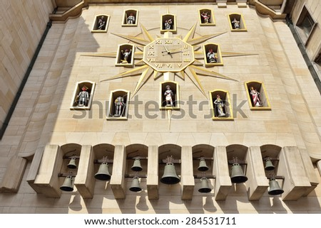 BRUSSELS, BELGIUM-MARCH 06, 2015: Wall clock decorated with statues and the carillon on the wall of Palace of Dynasty - stock photo