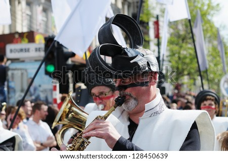 BRUSSELS, BELGIUM-MAY 19: An unknown participant with colored face plays music during Zinneke Parade on May 19, 2012 in Brussels. Belgium. This parade is a biennial free-attendance event - stock photo