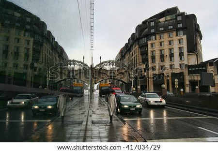 Brussels, Belgium - October 24, 2006: Traffic of cars and man with umbrella on a street leading through Brussels, Belgium on October 22, 2006 - stock photo