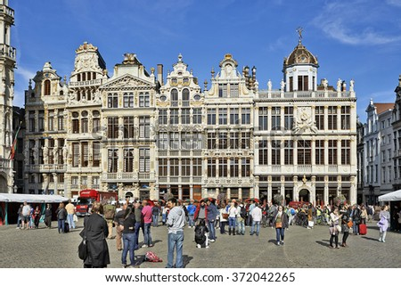 BRUSSELS,BELGIUM - SEPTEMBER 21, 2015: Many tourists enjoy the beauty of the Grand Place from Brussels in front of newly restored facades - stock photo