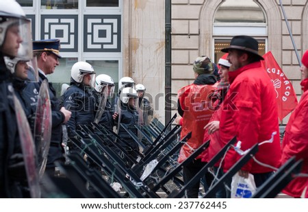 BRUSSELS - DECEMBER 15: National General Strike on December 15, 2014 in Belgium. Unions protesting against reforms proposed by Michel Government are confronted by riot police on Rue Royale, Brussels.  - stock photo