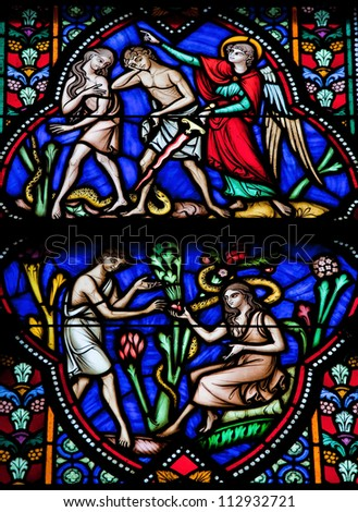 BRUSSELS - JULY 26: Stained glass window depicts Adam and Eve eating the Forbidden Fruit and being expelled from the Garden of Eden in the cathedral of Brussels on July, 26, 2012. - stock photo