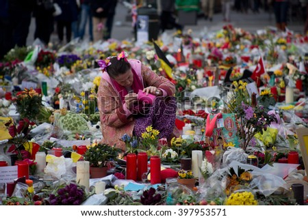 BRUSSELS - MARCH 29: Woman lighting a candle in front of the Stock Exchange to remember the victims of the terrorist attacks happened on March 22. Photo taken on March 29, 2016 in Brussels, Belgium.