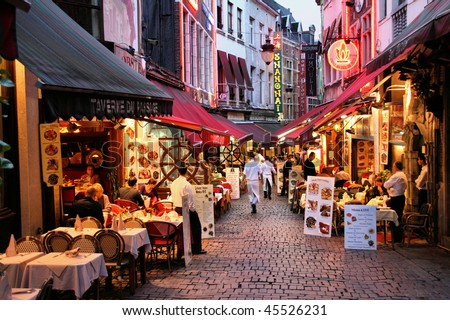 BRUSSELS - SEPTEMBER 1: Evening view of restaurants on September 1, 2009 in Brussels, Belgium. Rue des Bouchers street is famous for numerous restaurants offering cuisine from any place in the world. - stock photo