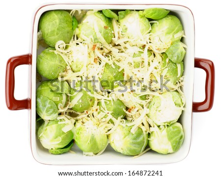 Brussels Sprouts Casserole in Brown Polka Dot Bowl with Grated Cheese and Spices isolated on white background. Top View - stock photo