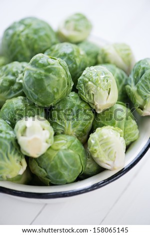 Brussels sprouts covered with water drops, vertical shot - stock photo