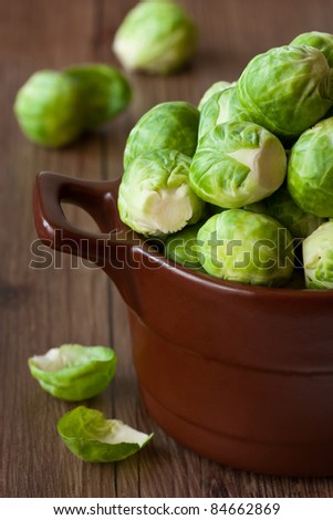 Brussels sprouts in a brown ceramic saucepan close-up. - stock photo
