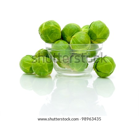 Brussels sprouts in a glass bowl closeup on a white background with reflection - stock photo