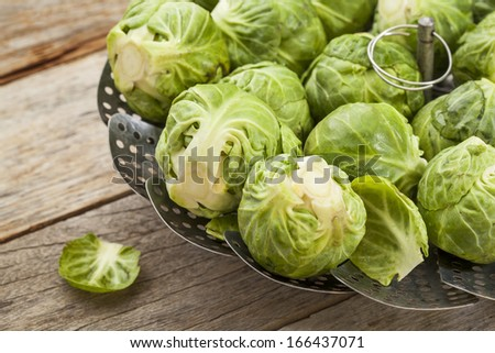 Brussels sprouts in a metal steamer basket on wooden table