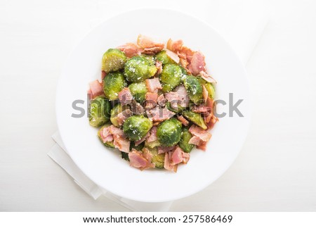 Brussels sprouts with bacon and parmesan on white wooden background top view. - stock photo