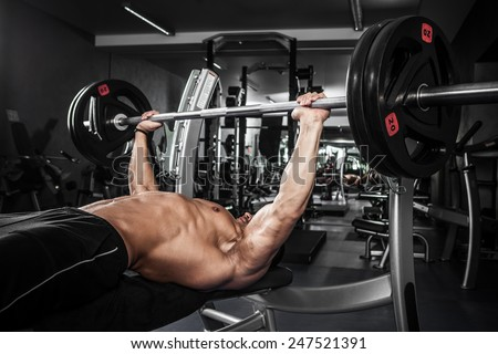 Brutal athletic man pumping up muscles on bench press - stock photo