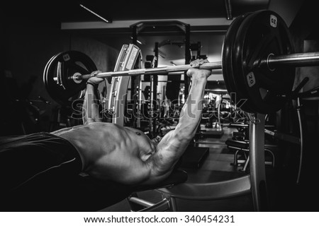 Brutal athletic man pumping up muscles on bench press in monochrome - stock photo