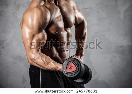 Brutal athletic man pumping up muscles with dumbbells - stock photo
