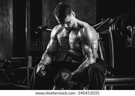 Brutal athletic man pumping up muscles with dumbbells in monochrome - stock photo