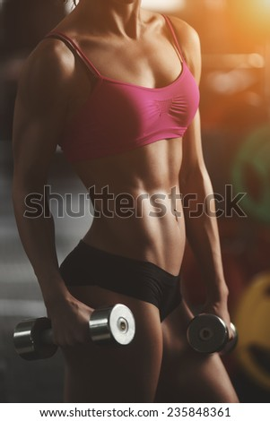 Brutal athletic woman pumping up muscles with dumbbells. Part of body. Athletic young woman doing a fitness workout - stock photo