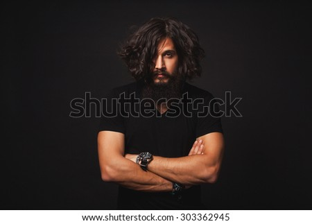 Brutal bearded man outdoor studio portrait.Cool businessman portrait outdoor,muscular body,rock n roll singer,trendy hairstyle man.handsome guy relaxing at grass