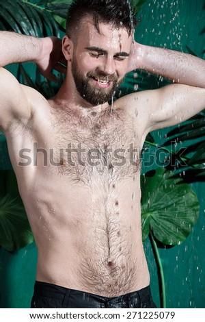 Brutal bearded man taking a shower - stock photo