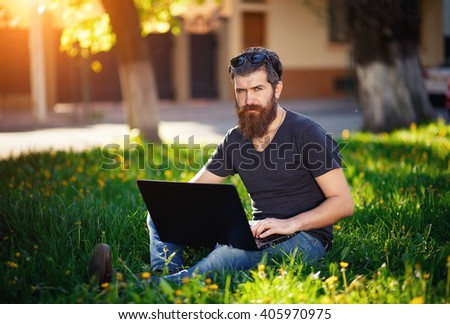 brutal bearded man with a mustache T-shirt, torn jeans and shoes, sitting with a laptop in the hands in the Spring Park Spring sunset