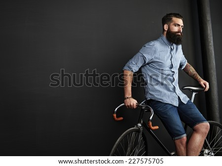 Brutal bearded man with vintage bicycle - stock photo