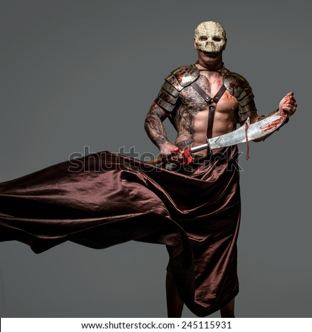 Brutal dangerous tattooed medievel fighter in skull mask in armor - stock photo