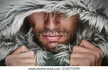 brutal face of a man with beard bristles and hooded winter - stock photo