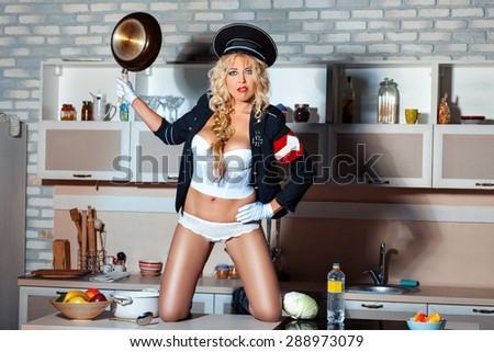 Brutal girl standing on a table in the kitchen. In her hand she holds a pan. She is wearing a military uniform humorous. - stock photo