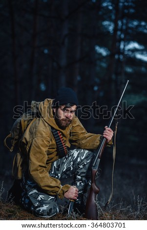 brutal hunter, bearded man in warm hat with a gun in his hand, a knife a backpack and smoking pipe in the dark wild forest in the autumn